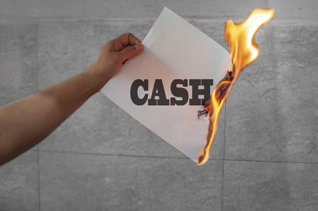 Burning cash text on burning paper in hand
