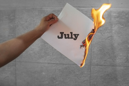 July word text on fire with burning paper in hand Stock Photo
