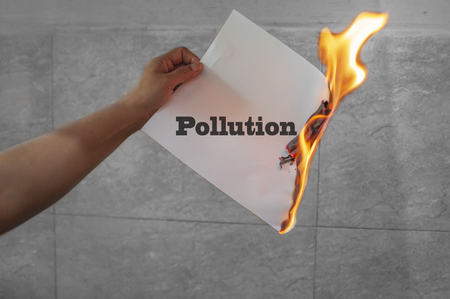 Pollution word text burning with fire on paper in hands Stock Photo