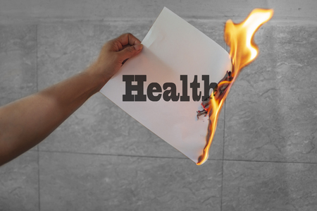 Burning health text on paper with flames in hand