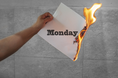 Monday word text on fire with burning paper in hand