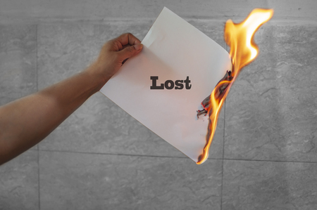 Lost text burning on paper in hand