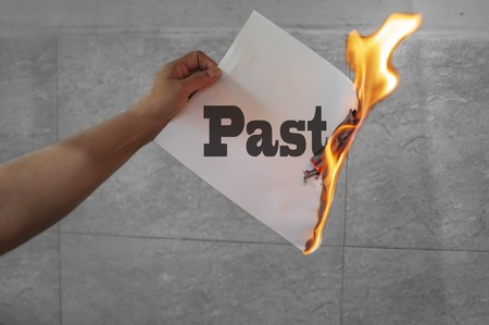 Burning past word text with fire on paper in hand