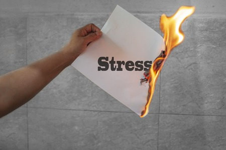 Stress word text on fire with burning paper in hand