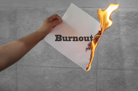 Burnout text with fire burning in the hands Stock Photo