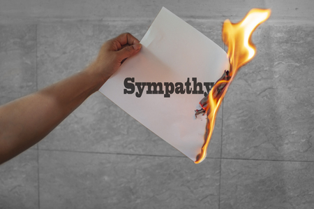 Sympathy word text on fire with burning paper in hand Stock Photo