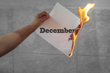 December word text on fire with burning paper in hand