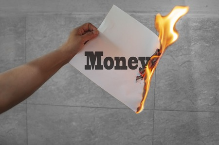 Money text on fire with burning paper in hand.