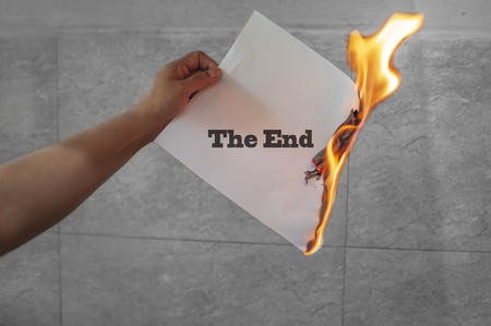 The end word text on fire with burning paper in hand Stock Photo