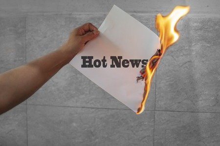 Hot news text on fire on paper in hands Stock Photo