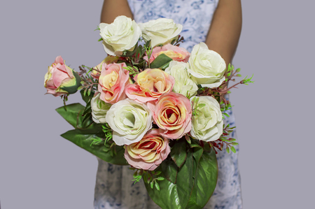 Fake flowers bouquet in hands and facing at the front on grey behind.