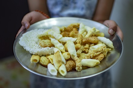 Serving indian fried snacks in plate and holding in hands