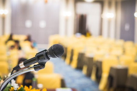 Microphone on stage in seminar room or speaking conference hall or educational seminar classroom with abstract blurred background. Selective focus on microphone.