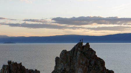 People at the top of the mountain. Beautiful sunset on the background Cape Burhan and Lake Baikal.