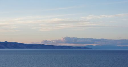 Beautiful sunset on a background of mountains on the shores of Lake Baikal.