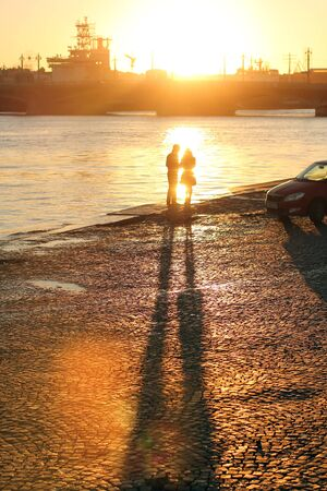 Sunset on the waterfront in the city. The girl and the guy on the waterfront at sunset. Banco de Imagens
