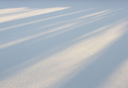 A snowy field and the sun's rays on the background of snow.