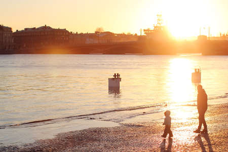 Dad with a child walking the city's waterfront. Spring evening in Saint Petersburg, the sunset on the Neva.