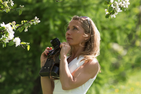 Beautiful blonde with blue eyes. Woman with a camera on a background of a blossoming garden. Sunny day, spring, photographer.