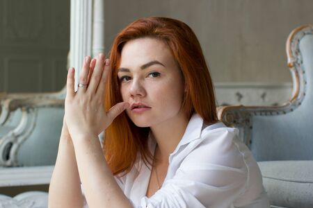 Portrait of a beautiful young woman. Young red-haired woman looking thoughtfully into the camera.