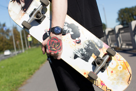 Skateboarder with a tattoo on his arm. The guy with the skateboard in hand is on the city's waterfront. Picture taken September 13, 2016 in St. Petersburg on the embankment of the river Ekateringofka.