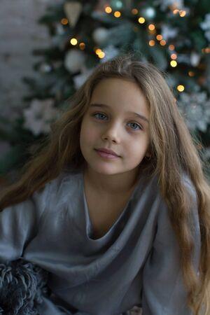 Amazingly beautiful girl on the background of the Christmas tree. Christmas Holidays. Banco de Imagens