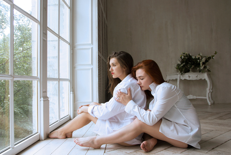 Two girls - a brunette and a redhead are sitting on the floor in a beautiful room. Amazingly beautiful girls in white shirts.