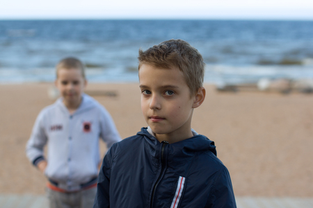 Two teenage boys stand on the beach by the sea. Brothers walk along the seashore during the summer holidays.