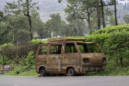 abandoned rust van parked in side of hill road in a foggy bright day Stock Photo