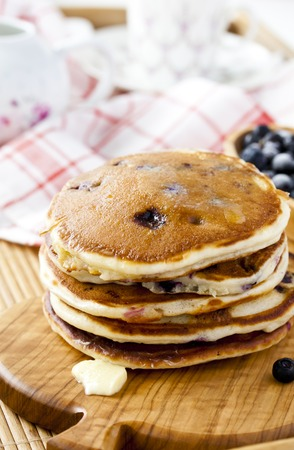 sweet and savoury: Pancakes with cottage cheese and blueberries on a wooden tray Stock Photo