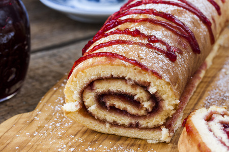 roulade: Biscuit roulade with cherry jam on a background of wooden boards
