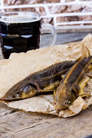 sturgeon: Hot smoked sturgeon with beer on wooden background