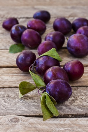 fresh plum scattered on a wooden table