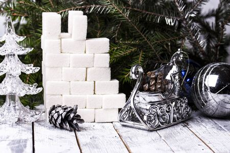 new construction: the castle tower of sugar cubes on the background of Christmas trees Stock Photo