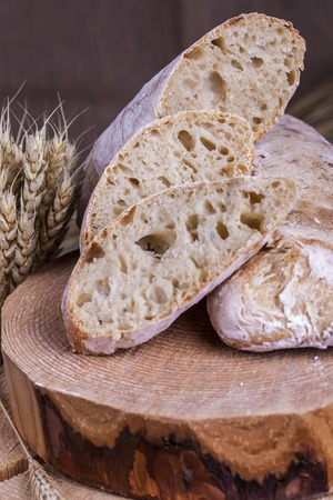 ciabatta: Homemade ciabatta with ears of wheat on a wooden table