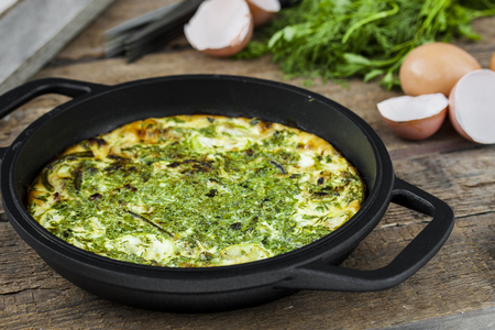baked omelet with zucchini and herbs in a frying pan