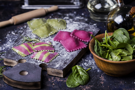 Making homemade ravioli with spinach and beets and stuffed seafood