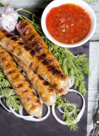Grilled sausage on a wooden board with sauce and vegetables