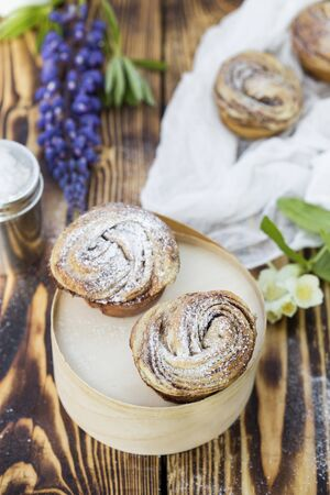 cinnamon swirl: Cruffins - buns from yeast dough in powdered sugar on wooden background