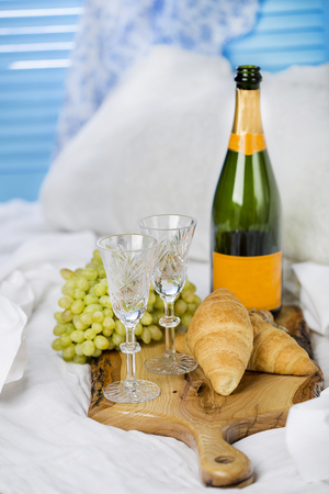 Breakfast in bed: croissants and champagne with fruit
