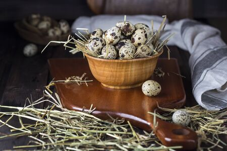 quail eggs in a wooden bowl on wooden background