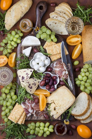 Different appetizers on the board: cheese, prosciutto, ham, bread, olives, grapes
