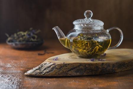 green tea in a glass teapot on dark background Stock Photo