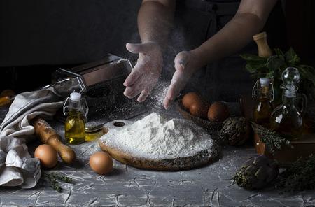 Vrouwelijke handen maken pasta donkere rustieke stijl Stockfoto