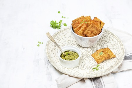 A bowl with homemade crispy cheese crackers on white background