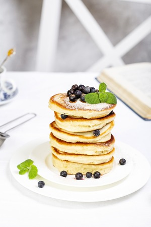 pancake stack decorated with blueberries and powdered sugar