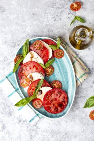 traditional Italian caprese salad with sliced tomatoes, mozzarella cheese, basil, olive oil
