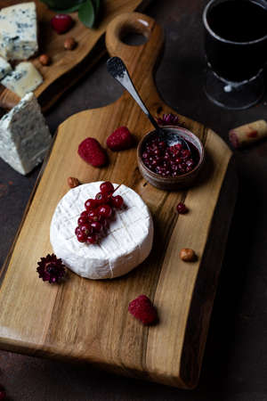 Different kinds of cheese on the wooden board with berries