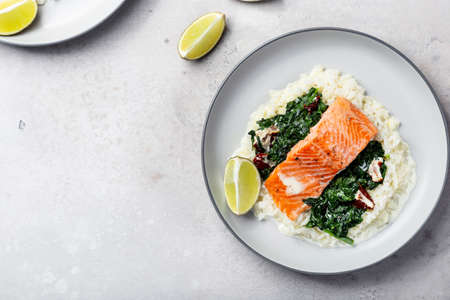 Salmon fillet with rice, spinach garnish and lime juice