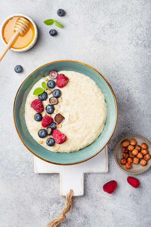 Tasty oatmeal with berries in bowl on white background Reklamní fotografie